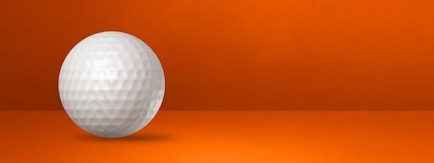 Biała piłeczka golfowa na białym tle na pomarańczowym banerze studio.