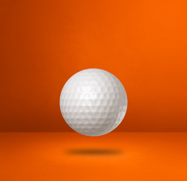 Biała piłeczka golfowa na białym tle na pomarańczowym tle studio.