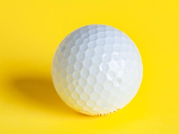 Biała piłeczka golfowa na żółtym, sport