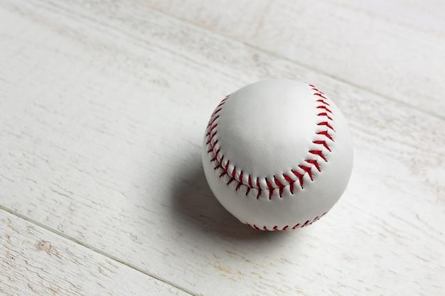 Biała piłka baseballowa zszyta czerwoną grubą.