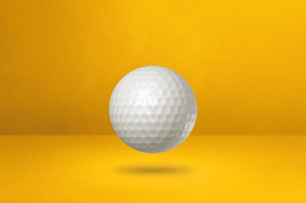 Biała piłka golfowa na żółtym tle