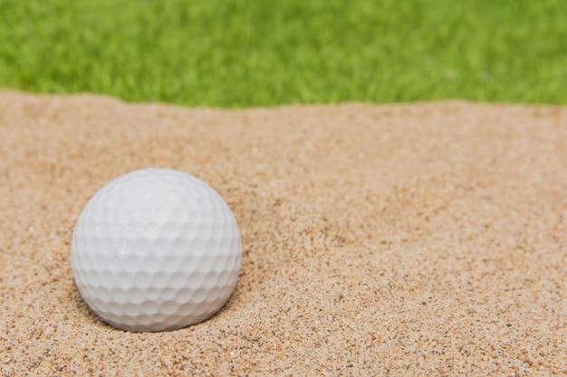 Biała piłka golfowa w bunkrze piasku na polu golfowym