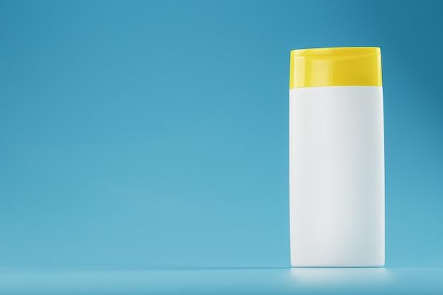 Biała plastikowa butelka z żółtą nakrętką z żelem szamponowym na niebieskiej powierzchni.