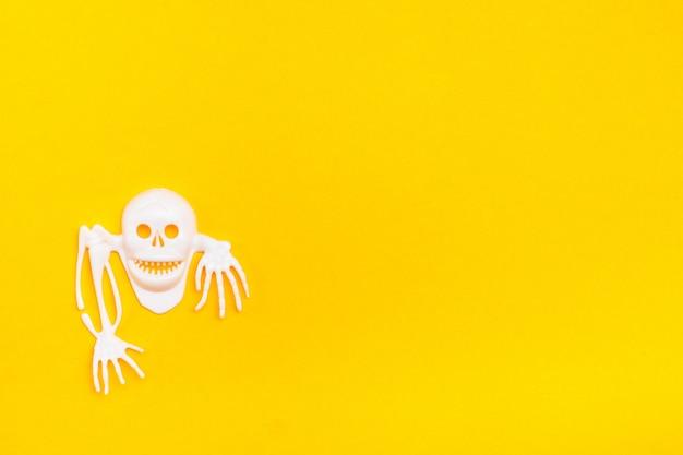 Biała plastikowa czaszka z kościami na żółtym tle kartonu. gotowa ilustracja halloween. skopiuj miejsce