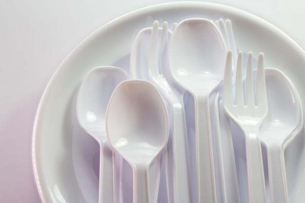 Biała plastikowa jednorazowa zastawa stołowa na białym tle