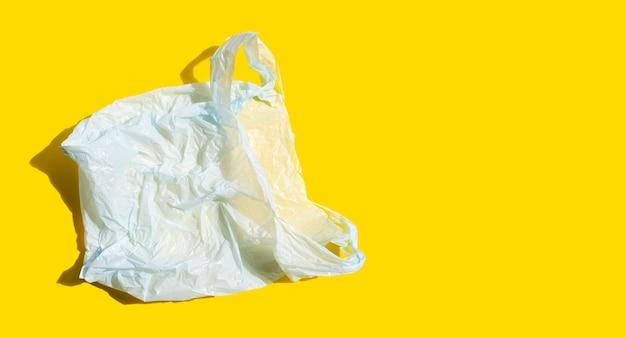 Biała plastikowa torba na żółtej powierzchni
