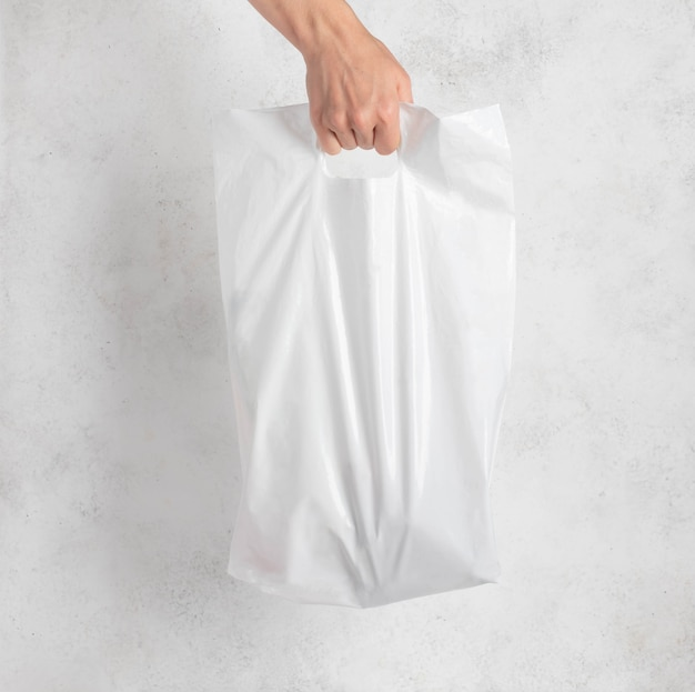 Biała plastikowa torba trzymana za rękę kobiety