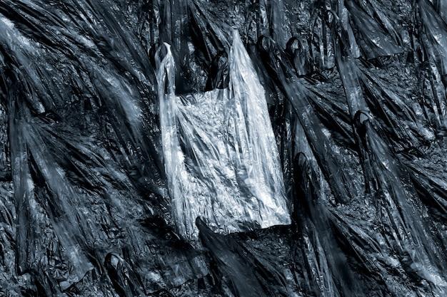 Biała plastikowa torebka na fakturze czarnych plastikowych torebek, plastikowe odpady przepełnione miastem