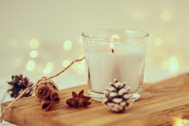 Biała płonąca świeczka z dekoracjami i girlandą zaświeca w bokeh na drewnianym stole. przytulny dom i hygge koncepcja