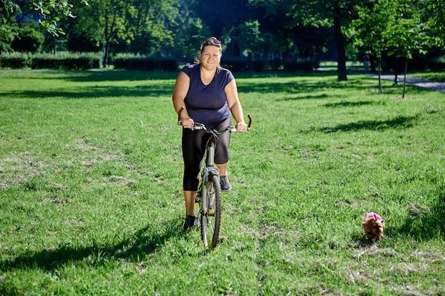 Biała plus size kobieta jedzie na rowerze w publicznym parku w słoneczny letni dzień