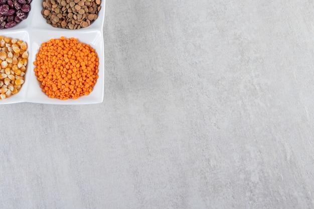 Biała płyta pełna surowej soczewicy, kukurydzy i fasoli na kamiennym tle.