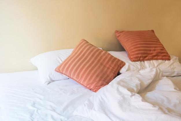 Biała poduszka i pomarańczowa poduszka na łóżku i pomarszczonym, niechlujnym kocem w zabytkowej sypialni