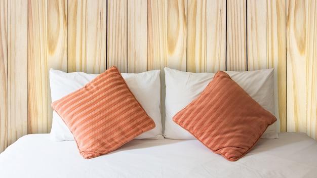 Biała poduszka i pomarańczowa poduszka na łóżku iz kocykiem w zabytkowej drewnianej sypialni