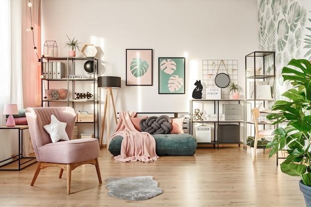 Biała poduszka na różowym fotelu w przytulnym wnętrzu sypialni z kocem na zielonym materacu