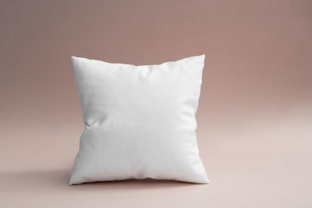 Biała poduszka na szaro-różowym tle.