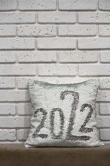 Biała poduszka ze srebrnymi błyskotkami z napisem 2022 poduszka z cekinami na tle ceglanego muru