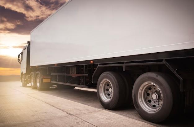 Biała półciężarówka na parkingu na wieczornym niebie słońca. przemysł towarowy transport drogowy transportem samochodowym.
