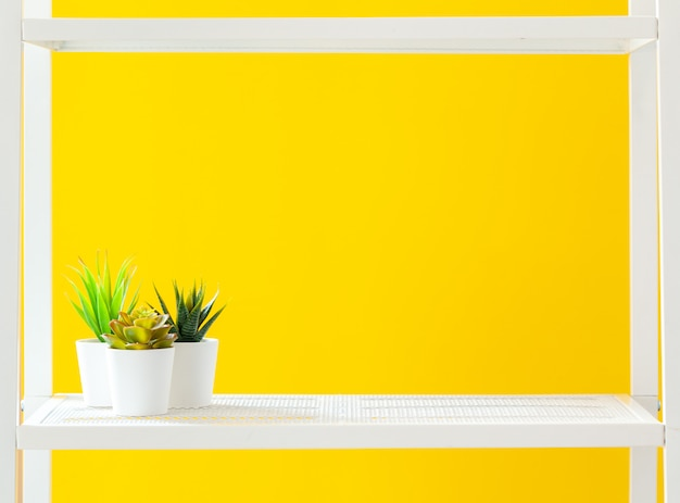 Biała półka z artykułami biurowymi na jasnożółtym