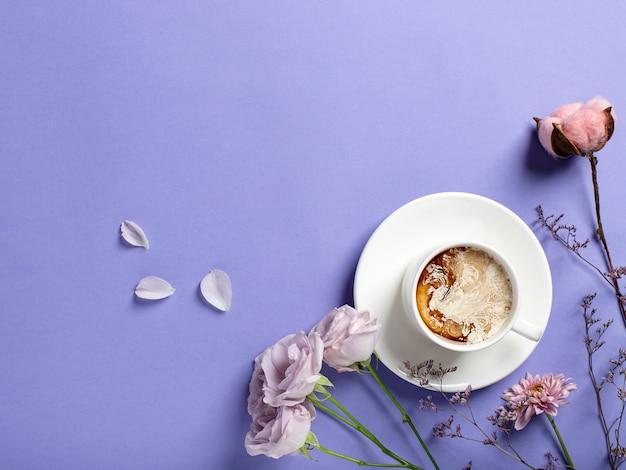 Biała porcelanowa filiżanka kawy i piękne kwiaty na fioletowym tle. koncepcja filiżanki kawy rano. leżał płasko, widok z góry, miejsce na tekst
