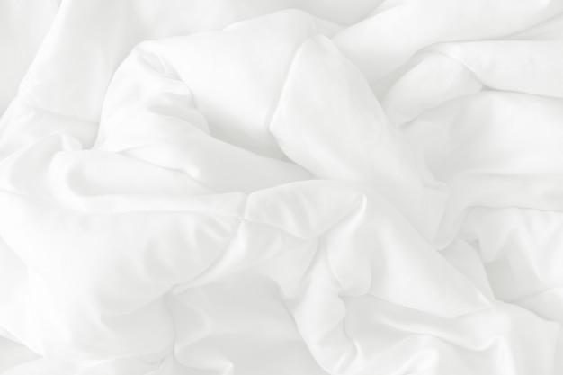 Biała pościel i pomarszczony, niechlujny koc w sypialni po porannym przebudzeniu