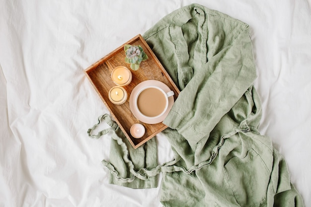 Biała pościel z szlafrokiem. taca z kawą i świecami. śniadanie w łóżku.
