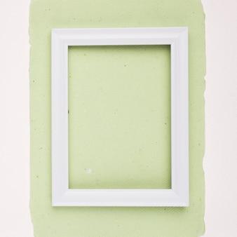 Biała prostokątna ramka na miętowym zielonym papierze na białym tle