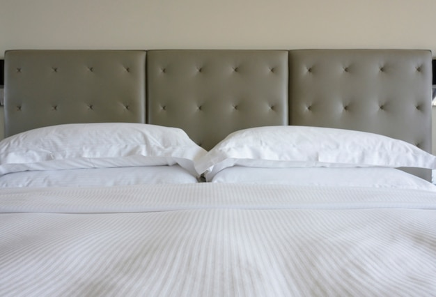 Biała prześcieradło i poduszka z głową w kolorze szarym w klasycznym stylu na tle ściany