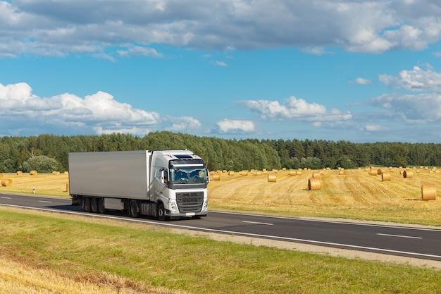 Biała przyczepa na autostradzie, na tle żółtego pola i błękitnego nieba. jest miejsce na reklamę
