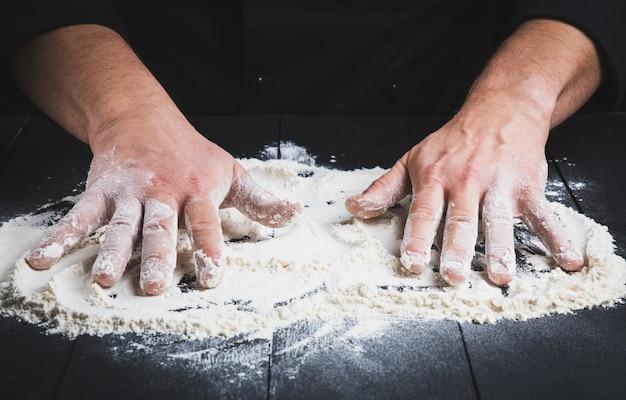Biała pszeniczna mąka na czarnym drewnianym stole i dwa męskich rękach