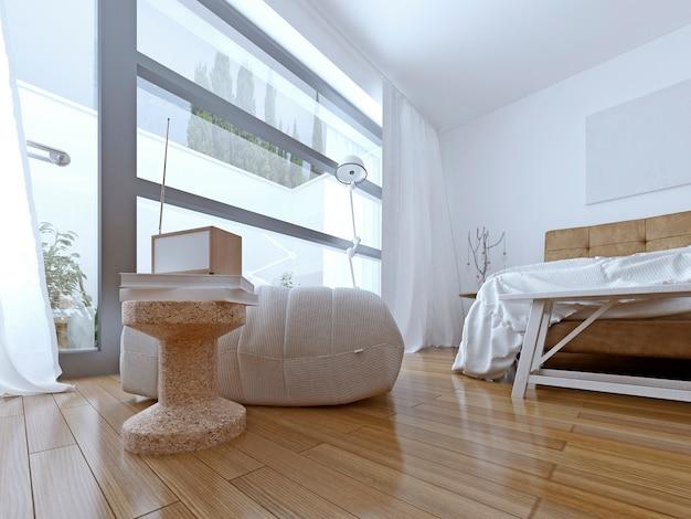 Biała pufa z niskim stołem i dekoracją w nowoczesnej sypialni.
