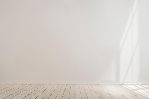 Biała pusta betonowa ściana z drewnianą podłogą