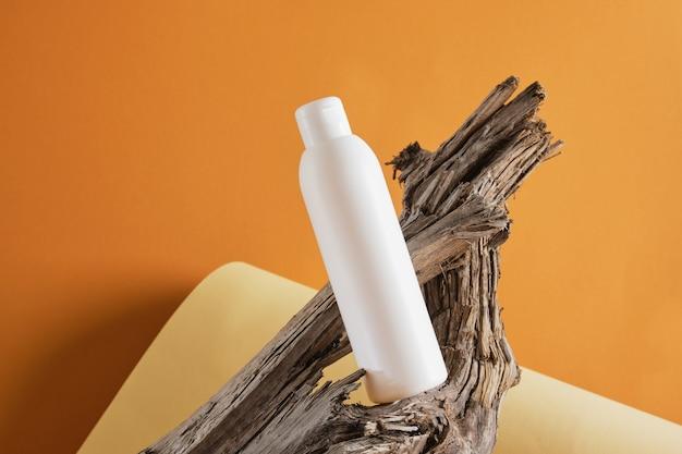 Biała pusta butelka na produkt kosmetyczny na betonowym podium na tle drewnianego drewna dryfującego, makiety brązowe tło