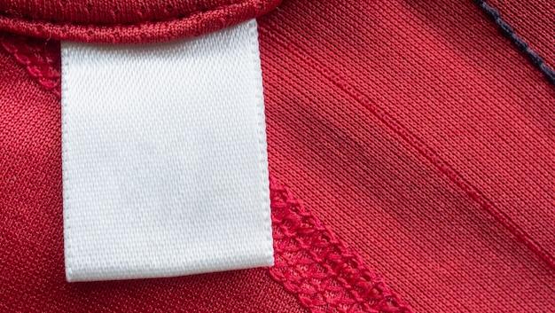 Biała, pusta etykieta na odzież do pielęgnacji prania na czerwonej koszulce sportowej z poliestru