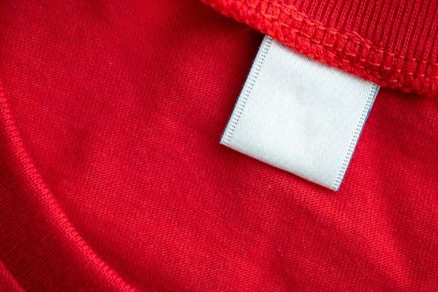 Biała pusta etykieta odzieżowa na nowym tle tekstury tkaniny czerwonej bawełnianej koszuli
