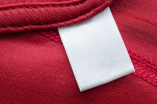 Biała pusta etykieta odzieży do pielęgnacji prania na tle czerwonej koszuli sportowej z poliestru
