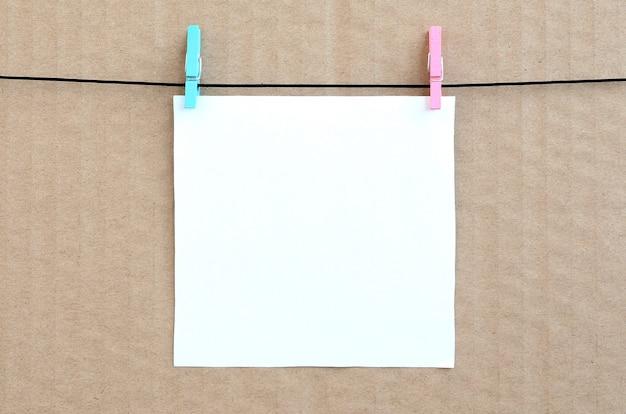 Biała pusta karta na arkanie na brown kartonowym tle.