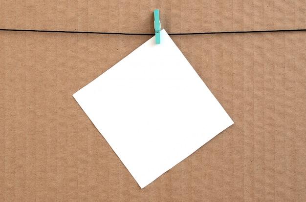 Biała pusta karta na arkanie na brown kartonowym tle