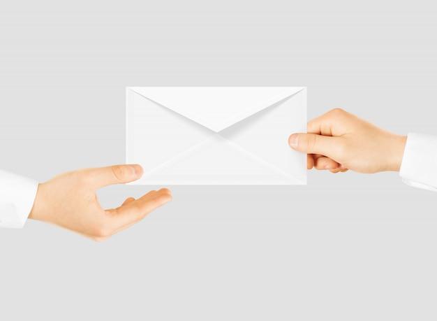 Biała pusta koperta daje rękę. wiadomość wyślij prezentację.