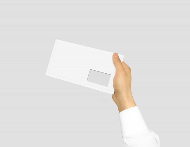 Biała pusta koperta makieta trzyma w ręku
