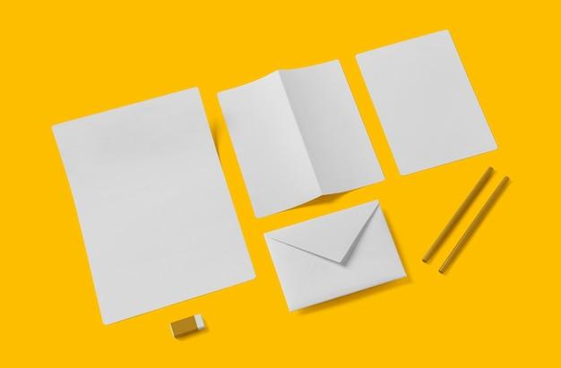 Biała pusta makieta papeterii, dodaj swój projekt. prosty powrót do koncepcji szkoły na żółtym tle.