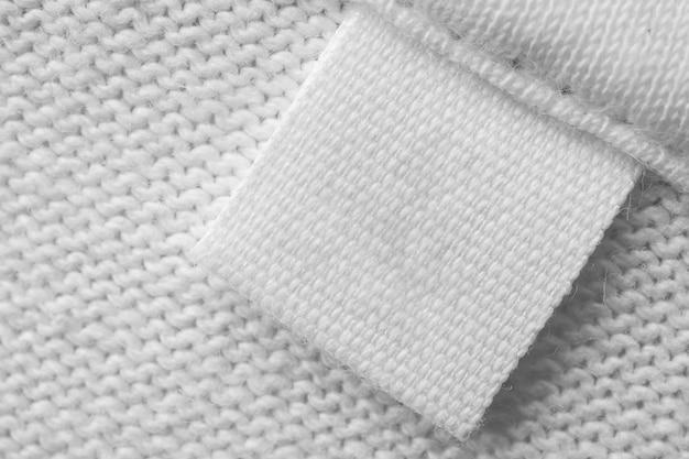 Biała pusta metka na odzież do pielęgnacji na bawełnianej koszuli