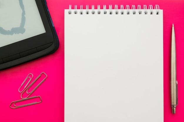Biała pusta otwarta notepad książka na pojęcia tle z biurowymi dostawami.