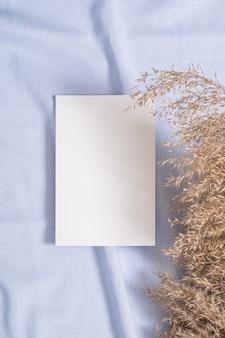 Biała pusta papierowa makieta z suchą trawą pampasową na niebieskim neutralnym kolorze tkaniny