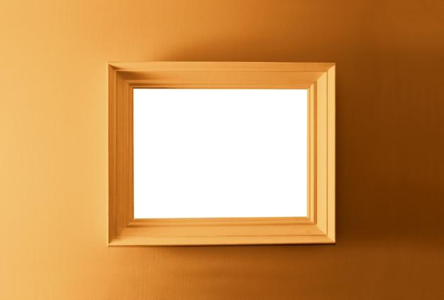 Biała pusta ramka na brązowej ścianie