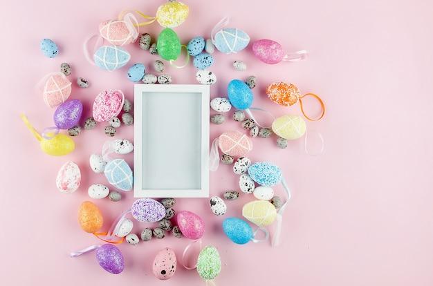 Biała pusta ramka z kolorowymi jajkami wokół na różowo