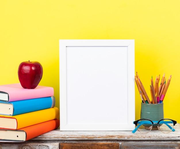 Biała rama na drewniane biurko z stosy książek i pastelowe tło