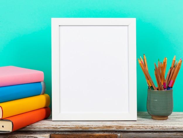 Biała rama na drewnianym biurku z stertą książki, pojęcie z powrotem szkoła