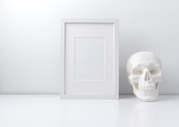Biała ramka i czaszka na półce z książkami lub biurku