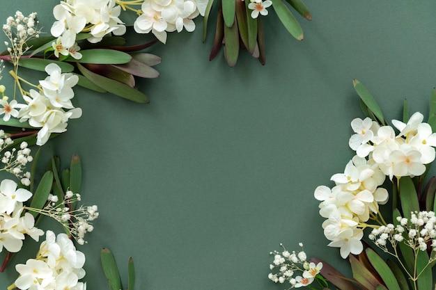 Biała ramka kwiatowa na zielonym tle