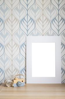 Biała ramka makiety na zdjęcie, wydruk grafiki, tekst lub napis, z dekoracjami pokoju dziecięcego i zabawkami. pusta rama na drewnianym stole z boku